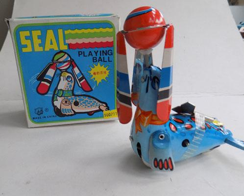 Tin wind up seal playing ball with box