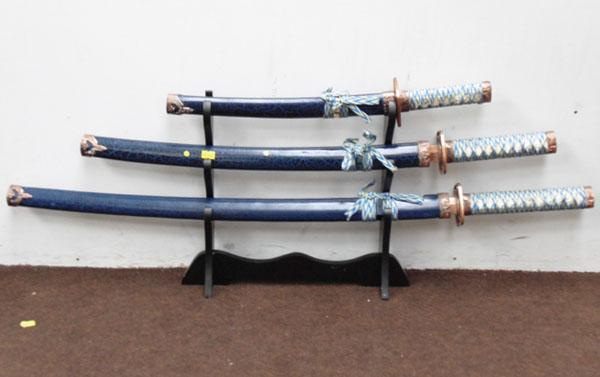 3x reproduction Samuri swords on stand