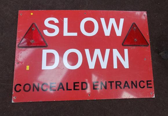 'Slow down concealed entrance' sign