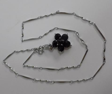 Silver chain and black flower pendant