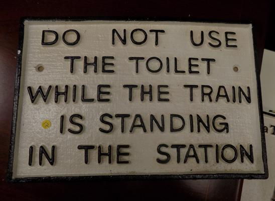 Cast iron toilet sign