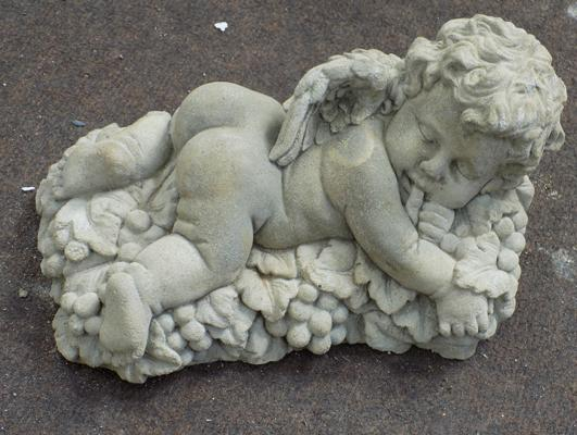 Baccus cherub - small cherub lying on a bed of grapes