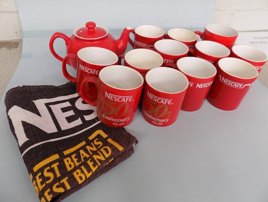 11 Nescafe mugs, 1 Kit Kat mug, 1 Red teapot and 1 Nescafe tea towel