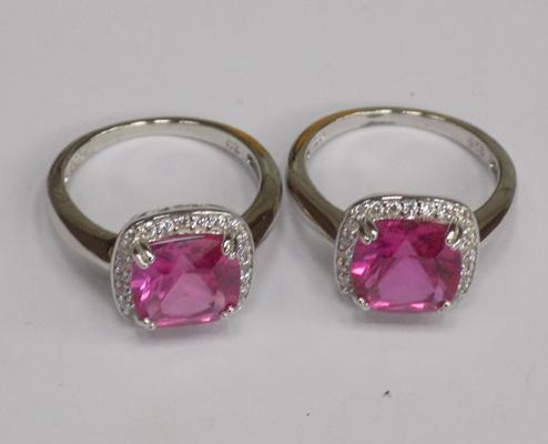Two silver rings with large pink stones