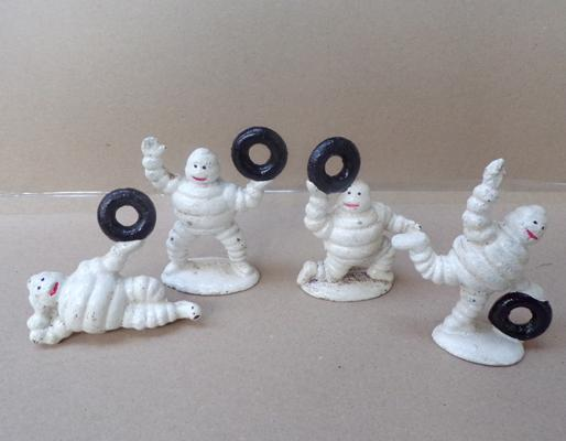 Four small Michelin men with tyres, cast iron