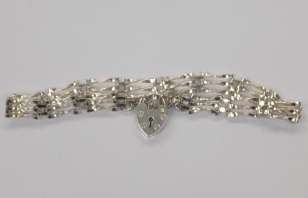 A sterling silver, three bar gate bracelet; with London hallmark