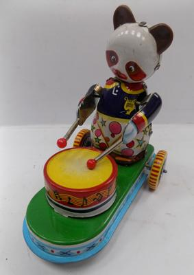 A vintage style, tinplate drumming panda