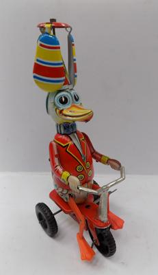 A vintage clockwork tinplate duck riding a bike; approximately 10 inches tall - marked West Germany