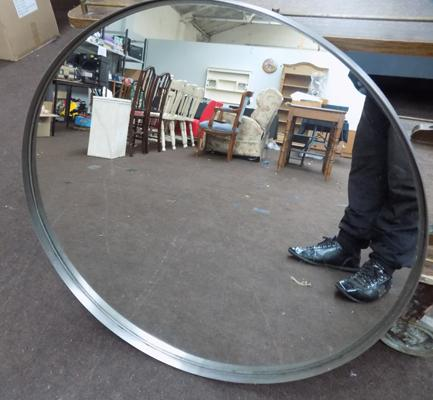 A large round, industrial/retail style mirror