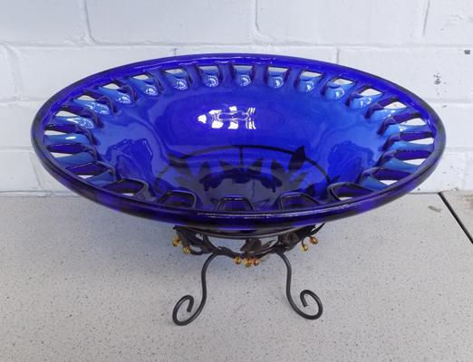 A blue glass bowl on metal stand