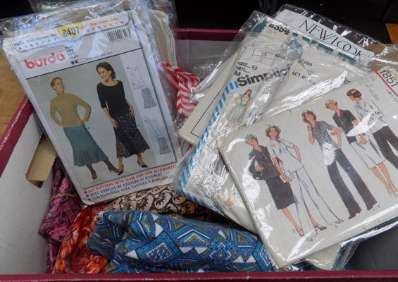 A box of vintage dress patterns and material