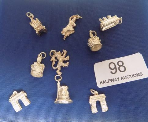 A collection of nine solid silver charms; including crowns and rearing lion