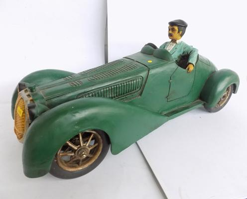 Large wooden model of man in vintage sport's car