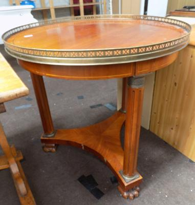Round tri-legged table with brass rim