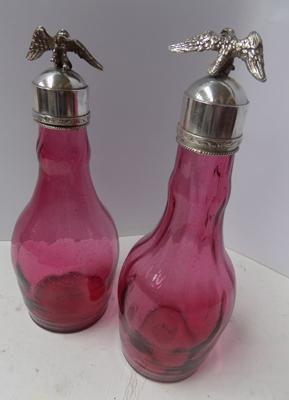 Pair of antique french import silver topped cranberry glass decanters. Eagle top.