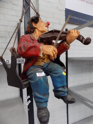 Clown on swing, playing violin