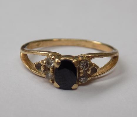 Yellow metal ring with dark blue stone