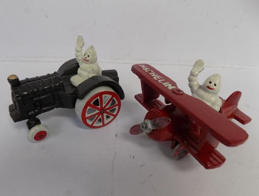 Cast iron Michelin man in By-plane (12cm) and man on tractor (11cm)