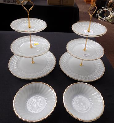 Two cake stands with matching bowls, all with gold rim