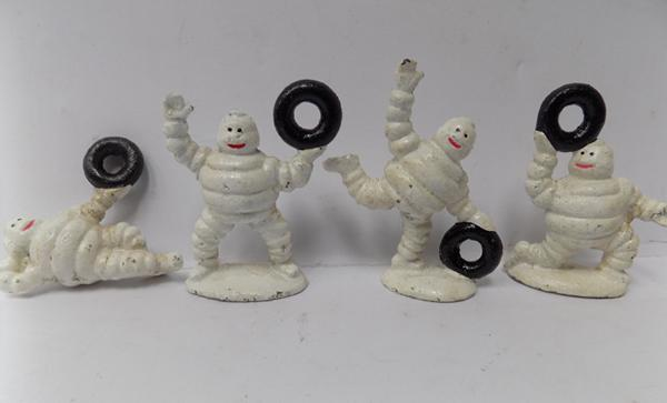 Cast iron, four small Michelin men with tyres