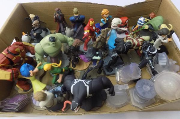 A large collection of Disney infinity figures and game pieces