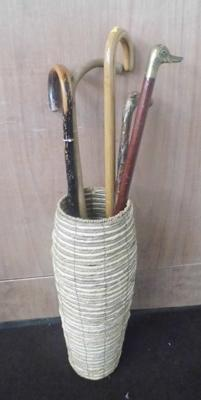 Selection of vintage walking sticks in wicker stand