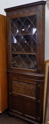 Leaded glass oak corner cabinet with carved panel