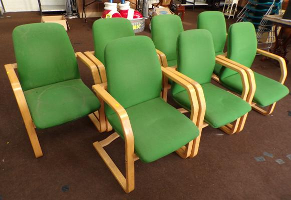 Seven green office chairs