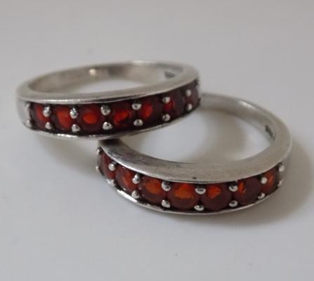 2 silver rings; 1x possibly opal orange and 1 red gemstone