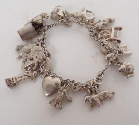Heavy silver charm bracelet with 21 charms 62.63gms