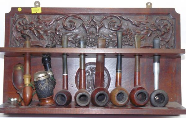 Carved oak pipe rack with assortment of pipes