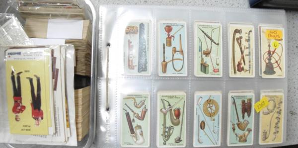 Pages of cigarette cards and tub of mixed cards