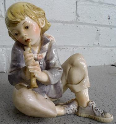 Resin figure of a child playing a flute