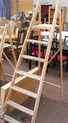 Set of wooden stepladders and a pasting table