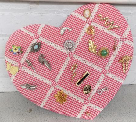 Collection of vintage brooches on heart shape pin board