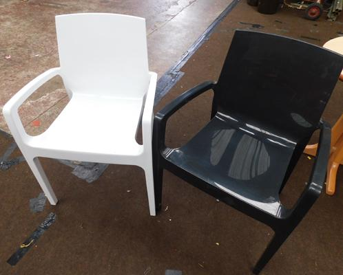 Two moulded plastic chairs, black & white, new, unused