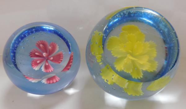 Pair of glass paperweights with flowers