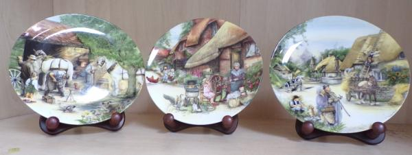Royal Doulton trio of Old Craft plates, The Spinner, The Thatcher & The Blacksmith + 3 plate holders