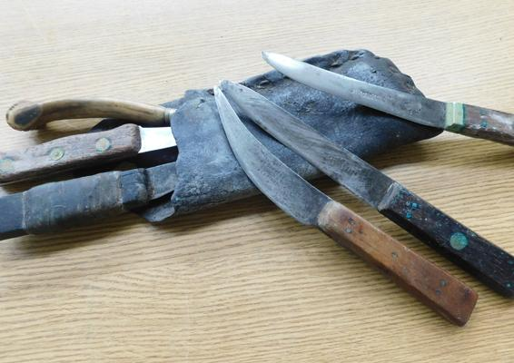 Collection of vintage butchers knives in leather sheath, including bone handled knife