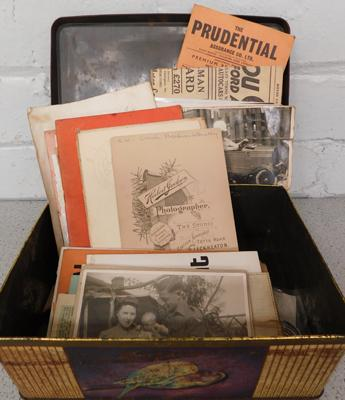 Biscuit tin with assorted ephemera, incl. postcards + two books